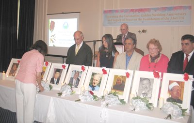 Legacy of Peace laying of flowers in front of pictures of honourees